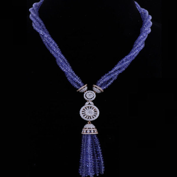 Multiple string beaded necklace with a diamond chakra pendant suspended on a black background.